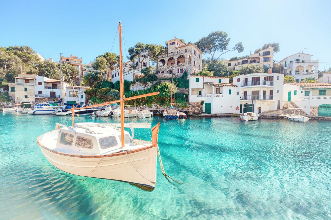 Ein Segelboot auf blauem Wasser vor weißen Häusern an der Küste von Mallorca.