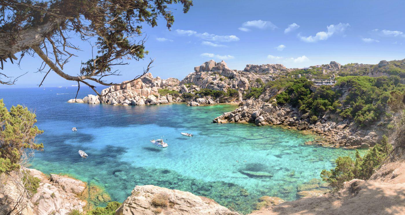 Eine Bucht mit türkisblauem Wasser und felsiger Küste auf Sardinien.