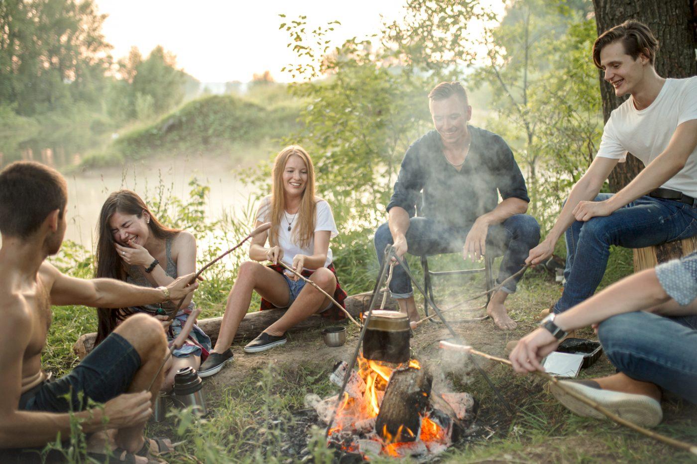 Eine Gruppe junger Menschen sitzt um ein Lagerfeuer.