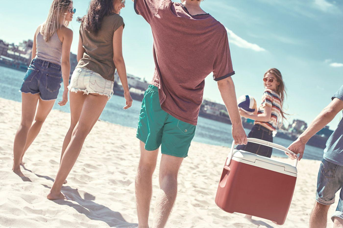 Junge Menschen am Strand tragen eine Kühlbox.