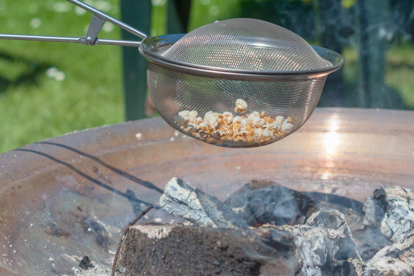 Popcorn wird über dem Lagerfeuer gemacht.