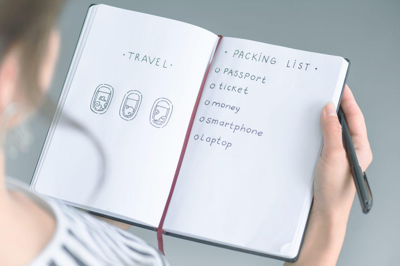 Eine Frau schreibt eine Packliste.