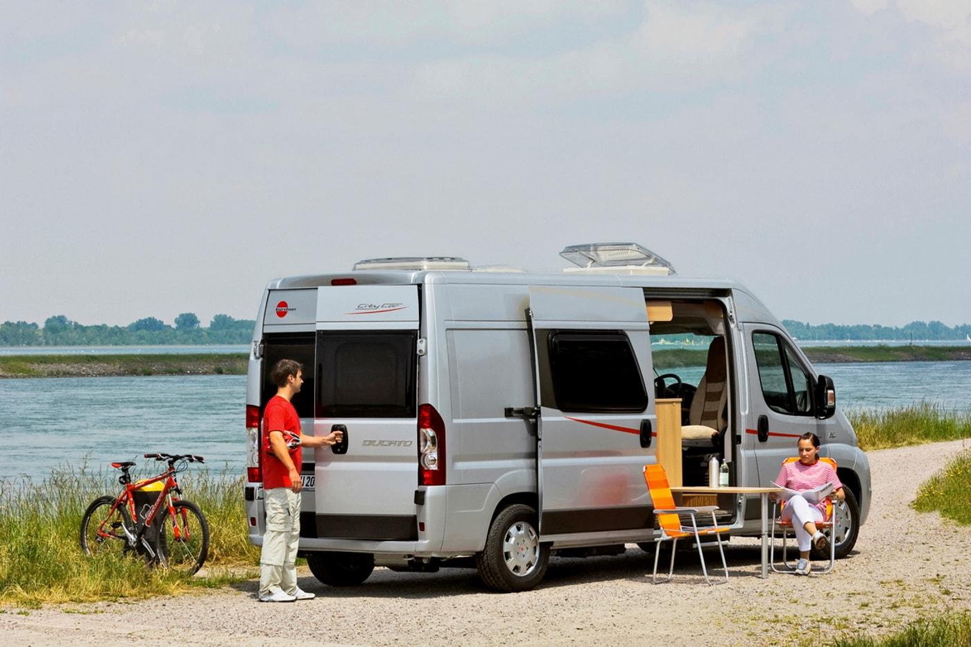 Zwei Campingreisende mit Kastenwagen machen Pause am Fluss