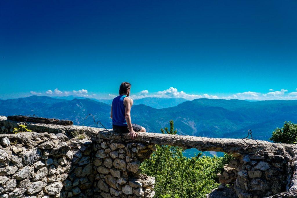 Mann auf Baumstamm in den Albanischen Alpen